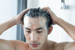 Closeup young man washing hair with with shampoo in the bathroom, health care concept, selective focus stock photography