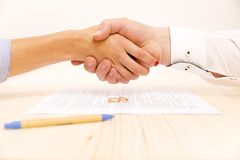 Closeup of a young man an a young woman shaking hands stock images