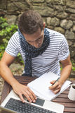 Closeup of young man working with laptop in outdoors. Attractive man working in your home garden Royalty Free Stock Images