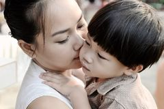 Closeup young mother kissing her son. Close up young asia mother kissing her son Royalty Free Stock Photography