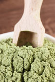 Closeup of young powder barley with wooden scoop, body detox concept Royalty Free Stock Photos