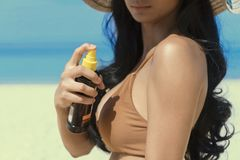 Closeup of Young sexy woman putting tanning oil on her arm, hand holding sunscreen suntan lotion spray skincare product at the. Beach, summer vacation stock images