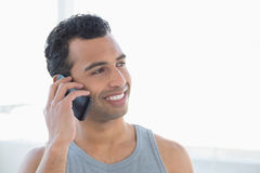 Closeup of a young smiling man using mobile phone Royalty Free Stock Photography