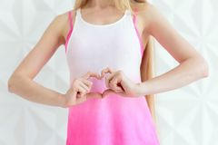 Young sporty woman making heart of fingers over white wall Royalty Free Stock Photo