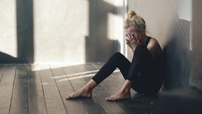 Closeup of young teenage girl dancer crying after loss perfomance sits on floor in hall indoors. Young teenage girl dancer crying after loss perfomance sits on royalty free stock photo