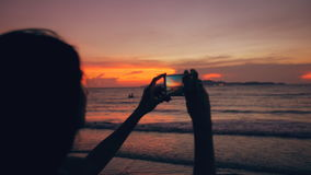 Closeup of young tourist woman photographs ocean view with smartphone during sunset at beach stock video