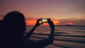Closeup of young tourist woman photographs ocean view with smartphone during sunset at beach. Shore Stock Photo