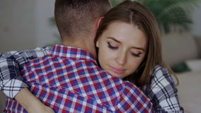 Closeup of young upset couple embrace each other after quarrel. Woman looking wistful and sad hug her boyfrined at home stock video