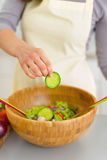 Closeup on young woman adding cucumber in salad Stock Image