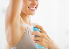 Closeup on young woman applying deodorant on underarm royalty free stock image