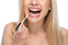 Closeup on young woman applying lip gloss Stock Image
