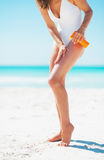 Closeup on young woman applying sun screen creme on beach Royalty Free Stock Images