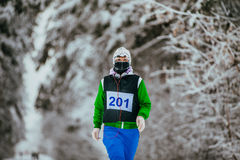 Closeup young woman athlete running snow-covered alley Stock Photography