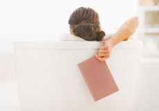 Closeup on young woman in bathtub holding book Royalty Free Stock Image