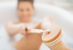 Closeup on young woman in bathtub using body brush Royalty Free Stock Photography