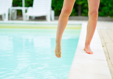 Closeup on young woman checking water in pool Stock Photography