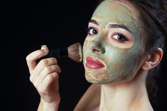Closeup of young woman with cosmetic mask on the face royalty free stock photos