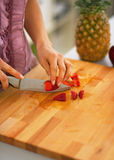 Closeup on young woman cutting strawberries in kitchen Royalty Free Stock Image