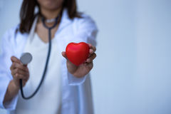Closeup of young woman doctor hands with ball heart shape. Red on white background Stock Photo