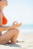 Closeup on young woman doing yoga on beach Stock Image