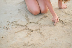 Closeup on young woman drawing on sand Royalty Free Stock Photo