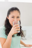 Closeup of a young woman drinking water in kitchen Stock Image