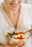 Closeup on young woman eating fresh fruits salad Stock Images