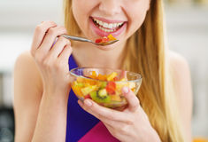 Closeup on young woman eating fresh fruits salad in kitchen Royalty Free Stock Photography
