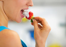 Closeup on young woman eating strawberry. In yogurt Stock Photography