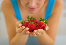 Closeup on young woman enjoying strawberries Royalty Free Stock Images