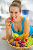 Closeup on young woman with fruits plate eating strawberry Royalty Free Stock Photo
