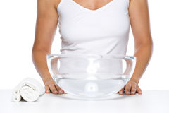 Closeup on young woman and glass bowl with water Royalty Free Stock Photo
