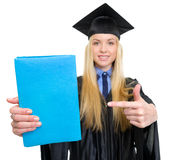 Woman in graduation gown pointing on book Royalty Free Stock Image
