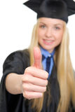 Цoman in graduation gown showing thumbs up Royalty Free Stock Images