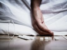 Closeup young woman hand lying on the bed with focus in pills. Overdose and suicide concept Stock Photography