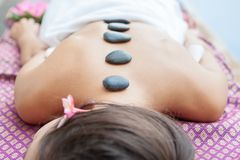 Closeup on young woman having hot stone massage on back in spa.  royalty free stock photo