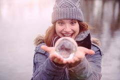 Closeup of young woman holding a glass sphere. Closeup of young woman outdoors holding a glass sphere Royalty Free Stock Images