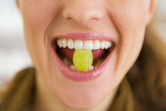 Closeup on young woman holding grape in mouth Royalty Free Stock Image