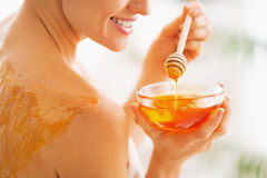 Closeup on young woman with honey on back holding honey plate Royalty Free Stock Photo