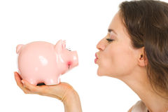 Closeup on young woman kissing piggy bank Stock Image
