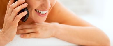 Closeup on young woman laying on massage table and talking cell Stock Photos