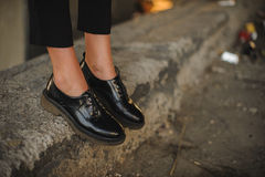 Closeup of young woman legs wearing black shoes Stock Image