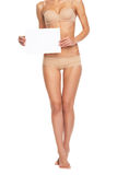 Closeup on young woman in lingerie showing blank paper sheet Royalty Free Stock Image