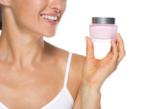 Closeup on young woman looking on cream bottle Stock Photography