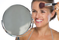 Closeup on young woman looking in mirror and makeup Stock Photos
