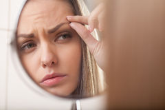 Closeup of young woman looking into mirror. Mirror reflection of beautiful girl eyebrow Stock Photo