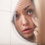 Closeup of young woman looking into mirror. Stock Photography