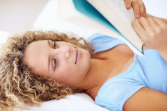 Closeup of a young woman lying on bed reading book Royalty Free Stock Photos