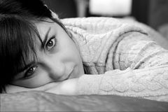 Closeup of young woman lying in bed thinking about lost love unhappy black and white Stock Image