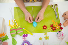 Closeup on young woman making easter decoration Royalty Free Stock Photo